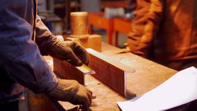 Construction plant. A man working with a small iron detail. Mid shot stock photos