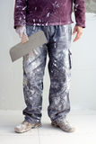 Construction plaster plaster man dirty trousers. Construction plastering man dirty trousers with trowel in hand Stock Image
