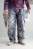 Construction plaster plaster man dirty trousers. Construction plastering man dirty trousers with trowel and saw in hand Royalty Free Stock Image