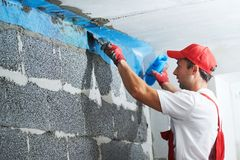 Plasterer worker protecting corner with mesh. building technology royalty free stock photo