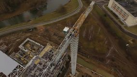 Construction platform aerial view in autumn. Construction crane in the city of Minsk autumn aerial survey building site gloomy mood stage construction stock video