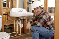 Construction Plumber. A construction plumber installing bathroom fixtures in a home under construction Royalty Free Stock Image