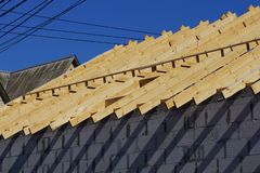 Building a house of wooden planks and gray bricks against a blue sky. Construction of a private house of brown wooden boards and gray bricks against a blue sky royalty free stock image