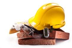 Construction profession. Yellow working hard hat, goggles, gloves, red bricks on a white background Stock Image