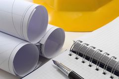 Construction project drawings. Agenda, helmet and pen Stock Photos