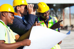 Construction project manager. Project manager using binoculars looking at the construction site with workers Stock Image