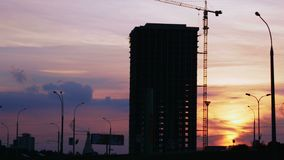 Construction project silhouette against sunset sky. City landscape with cars and construction site stock footage