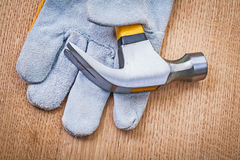 Construction protective glove and claw hammer on wooden board Stock Photo
