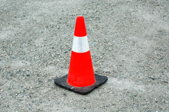 Construction Pylon. Orange, white and black construction pylon sitting on gravel stock photo