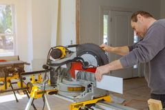 Construction remodeling home cutting wooden trim base molding on with circular saw. Saws a man lumber equipment woodwork machine blade building hand industrial royalty free stock image
