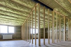 Construction and renovation of big light spacious empty room with oak floor, walls and ceiling insulated with rock wool, heating stock image
