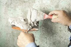 Construction and renovation concept. Hands of worker with plastering tools. Construction and renovation concept.Building worker with spatula and mortar Stock Photo