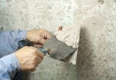 Construction and renovation concept. Hands of worker with plastering tools. Construction and renovation concept.Building worker with spatula and mortar Royalty Free Stock Images