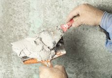 Construction and renovation concept. Hands of worker with plastering tools during of work. Construction and renovation concept.Building worker with spatula and Stock Images