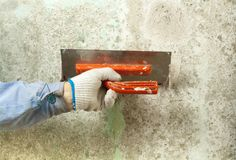 Construction and renovation concept. Hand of man in glove with trowel during repair of wall. Construction and renovation concept. Hand of man in glove during Stock Photography