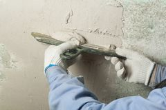 Construction and renovation concept. Hand of man in glove with trowel during repair of wall. Construction and renovation concept. Hand of man in glove during Royalty Free Stock Image