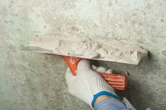 Construction and renovation concept. Hand of man in glove with trowel during repair of wall. Construction and renovation concept. Hand of man in glove during Stock Image