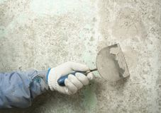 Construction and renovation concept. Hand of worker with plastering tools. Construction and renovation concept. Hand of worker in glove with spatula during Royalty Free Stock Photo