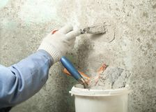 Construction and renovation concept. Hand of worker with plastering tools. Construction and renovation concept. Hand of worker in glove with spatula during Royalty Free Stock Photos