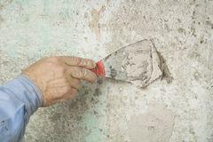 Construction and renovation concept. Hand of worker with plastering tools. Construction and renovation concept.Building worker with spatula and mortar Royalty Free Stock Photos