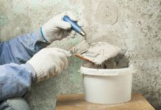 Construction and renovation concept. Hands of worker in gloves with plastering tools. Construction and renovation concept. Hands of worker in gloves with Royalty Free Stock Photos