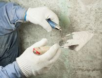 Construction and renovation concept. Hands of worker in gloves with plastering tools. Construction and renovation concept. Hands of worker in gloves with Royalty Free Stock Photo