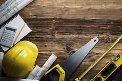 Construction and renovation concept. Place for typography or text. Blueprints and building contractor tools on wooden table. Top view royalty free stock photography