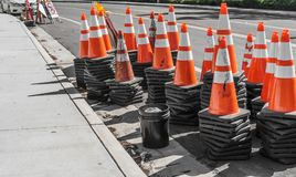Orange and white construction cones stacked on side of the street. Stock Photography