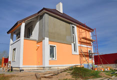 Construction or repair of the rural house with balcon, eaves, windows, chimney, roofing, fixing facade, insulation and painting. Construction or repair of the Stock Photo