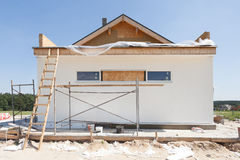 Construction or repair of the rural house with insulation, eaves. Windows, garage,chimney, roofing, fixing facade,plastering and white walls Royalty Free Stock Photos
