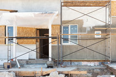 Construction or repair of the rural house with insulation, eaves. Windows, garage,chimney, roofing, fixing facade,plastering and white walls Stock Photography