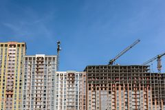 Construction of residential building. yellow cranes against blue royalty free stock image
