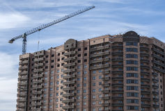 Construction of residential complex. Under construction high-rise residential complex, and standing next to the tower crane Stock Photo