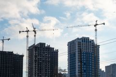 Construction of residential multi-storey buildings with the help of four tower cranes.  stock photos