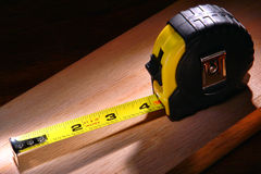 Construction Retracting Tape Measure on Wood Board royalty free stock photography