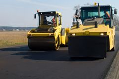 Construction of road. The asphalt spreader and the bulldozer build road stock image