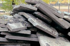 A large pile of broken, gray biton slabs lies on the ground. stock photos