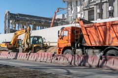 Construction and road machinery: an excavator and a dump truck at a construction site for the demolition of a building stock photo