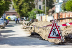 Construction roadwork on street in city. Red safety sign warns a Stock Photos