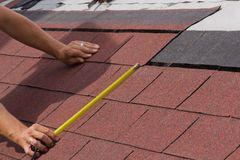 Construction of a roof. Construction of asphalt shingles on a roof of wood Royalty Free Stock Images