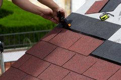 Construction of a roof. Construction of asphalt shingles on a roof of wood Royalty Free Stock Photo