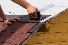 Construction of a roof. Construction of asphalt shingles on a roof of wood Stock Photo