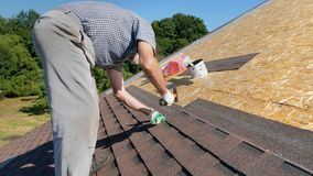 Construction of the roof. Soft roof, shingles. Roofer. Construction of the roof. Soft roof, shingles. Builder in white gloves, puts the sheets of shingles and stock video