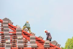Construction roofer installing roof tiles at house building site. Construction roofer installing roof tiles at house building construction site royalty free stock photo
