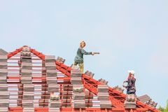 Construction roofer installing roof tiles at house building site. Construction roofer installing roof tiles at house building construction site stock photography
