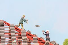 Construction roofer installing roof tiles at building site. Construction roofer installing roof tiles at house building site royalty free stock images