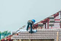 Construction roofer installing roof tiles at building site. Construction roofer installing roof tiles at house building site royalty free stock photos