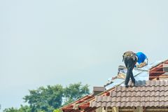 Construction roofer installing roof tiles at building site. Construction roofer installing roof tiles at house building site royalty free stock photo