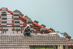 Construction roofer installing roof tiles at building site. Construction roofer installing roof tiles at house building site stock image