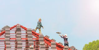Construction roofer installing roof tiles at building site. Construction roofer installing roof tiles at house building site stock photos